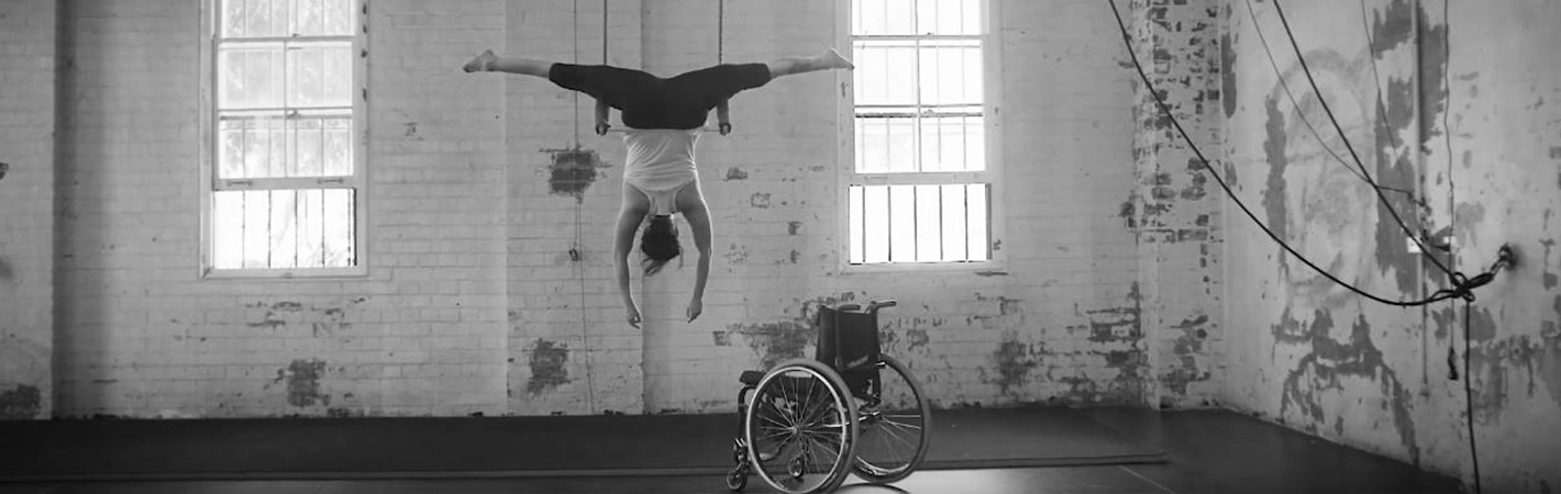 AAAA 2019 winner Lauren Watson. She is balanced on an aerial apparatus. Her wheelchair off to one side on the ground beneath her