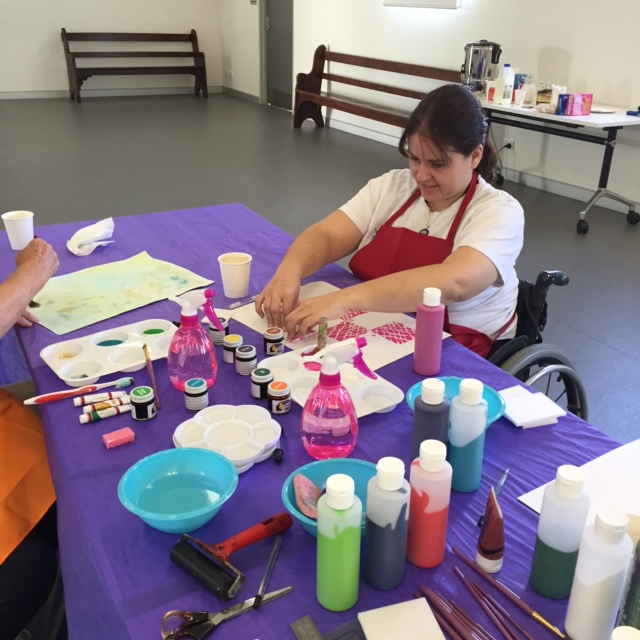 Earlier workshop participant sitting at table while working with stencils and surrounded by paint bottles