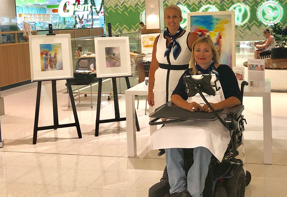 Two women, one in wheelchair, and one standing. Easels arranged behing showing watercolour artwork