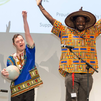 Alex and Tichawona standing with arms raised on stage after a performance