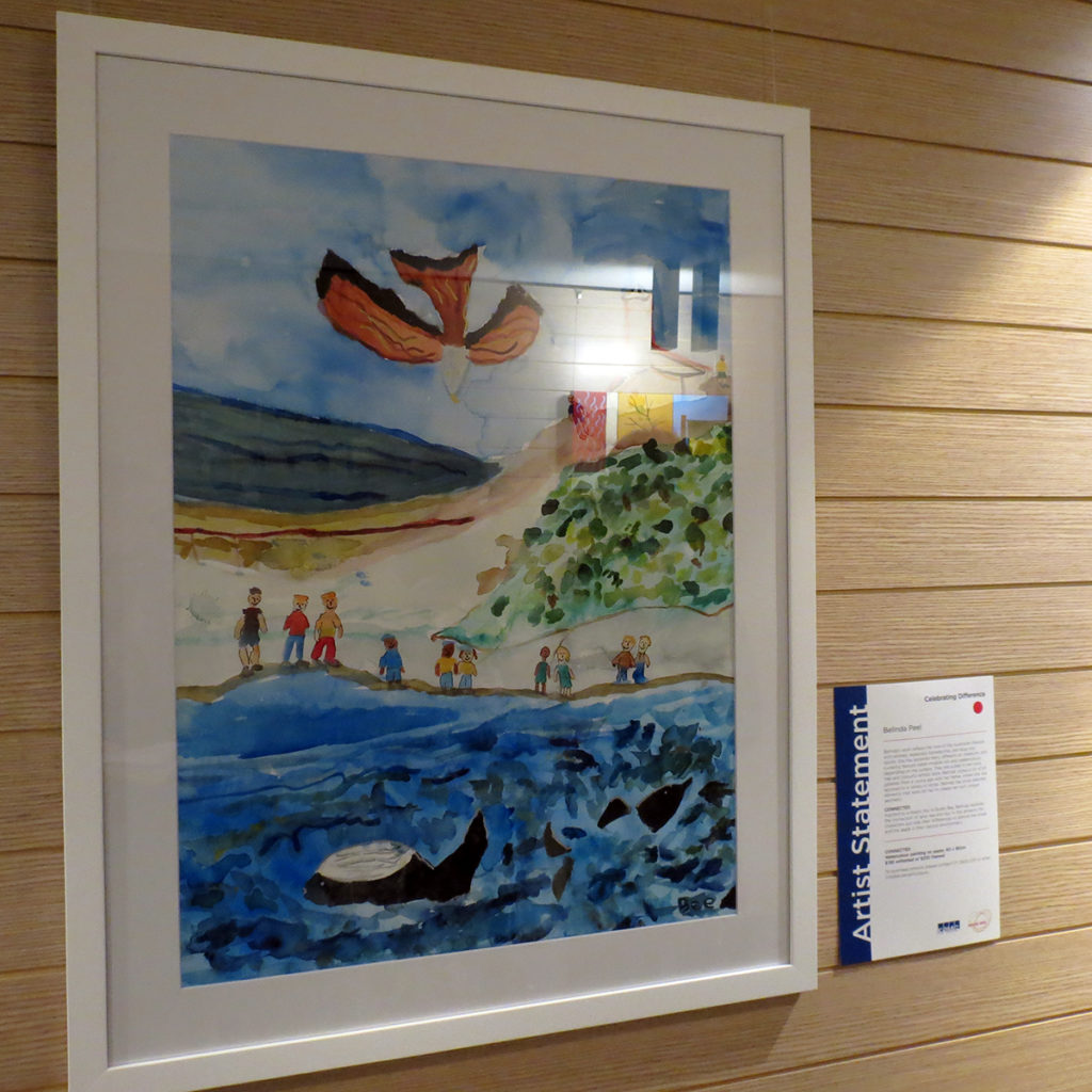 Framed watercolour painting hung on a wall depicting a day a the beach