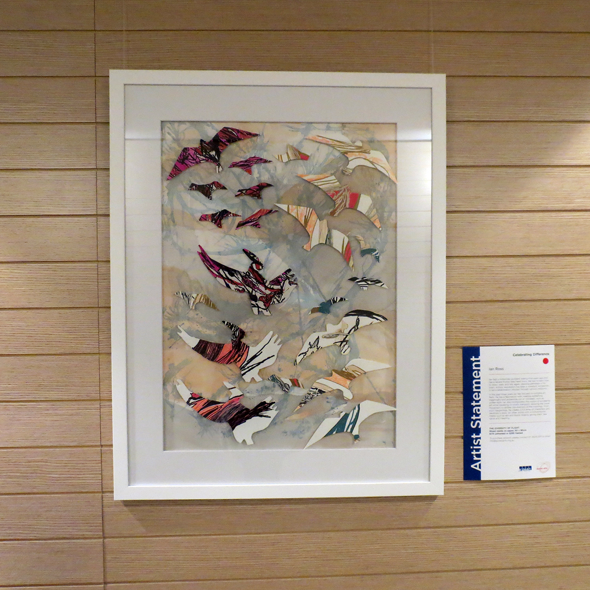 Framed artwork on a wall with cut out paper birds of different sizes