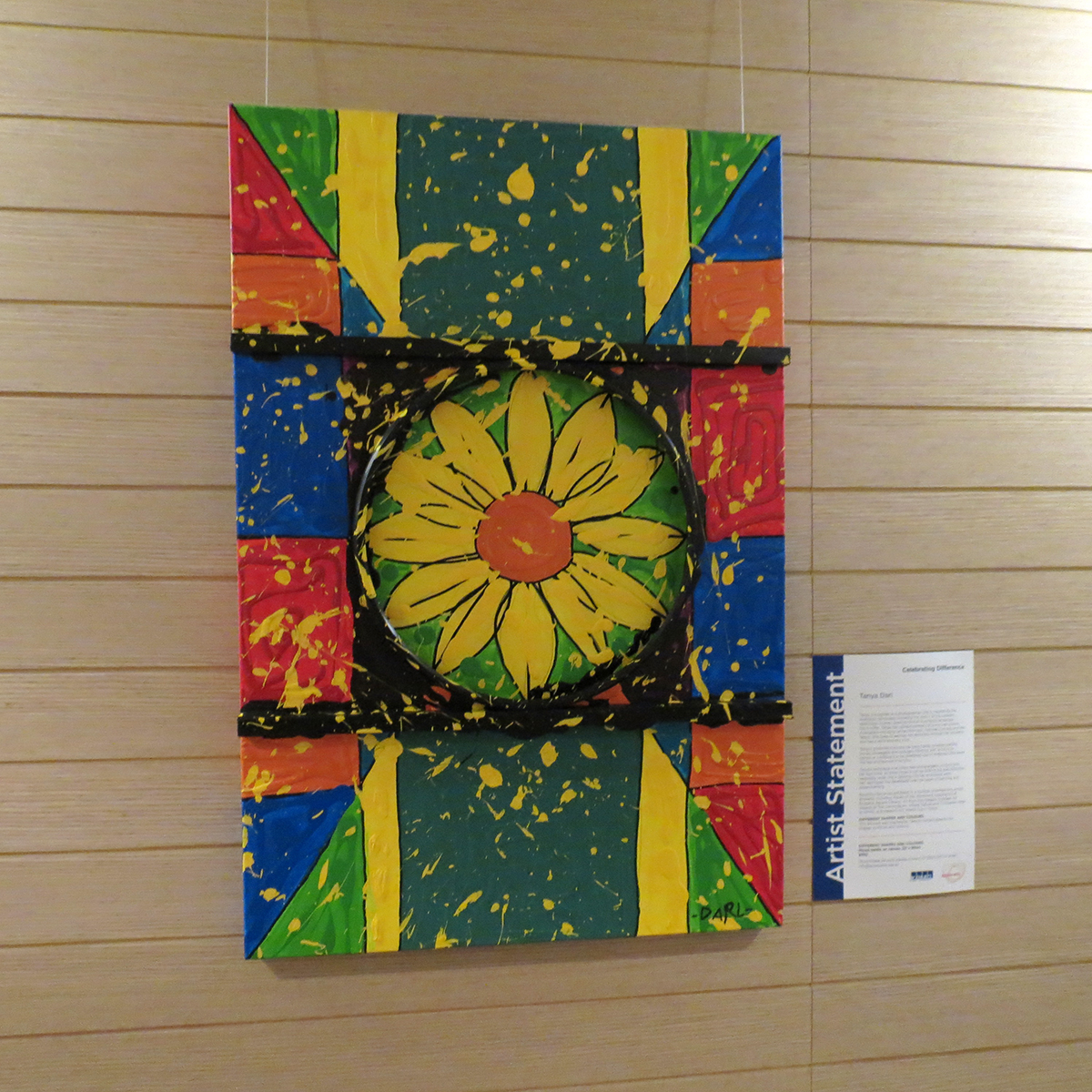 Canvas hung on a wall with a sunflower painted in the centre and bright blocks of colour around it