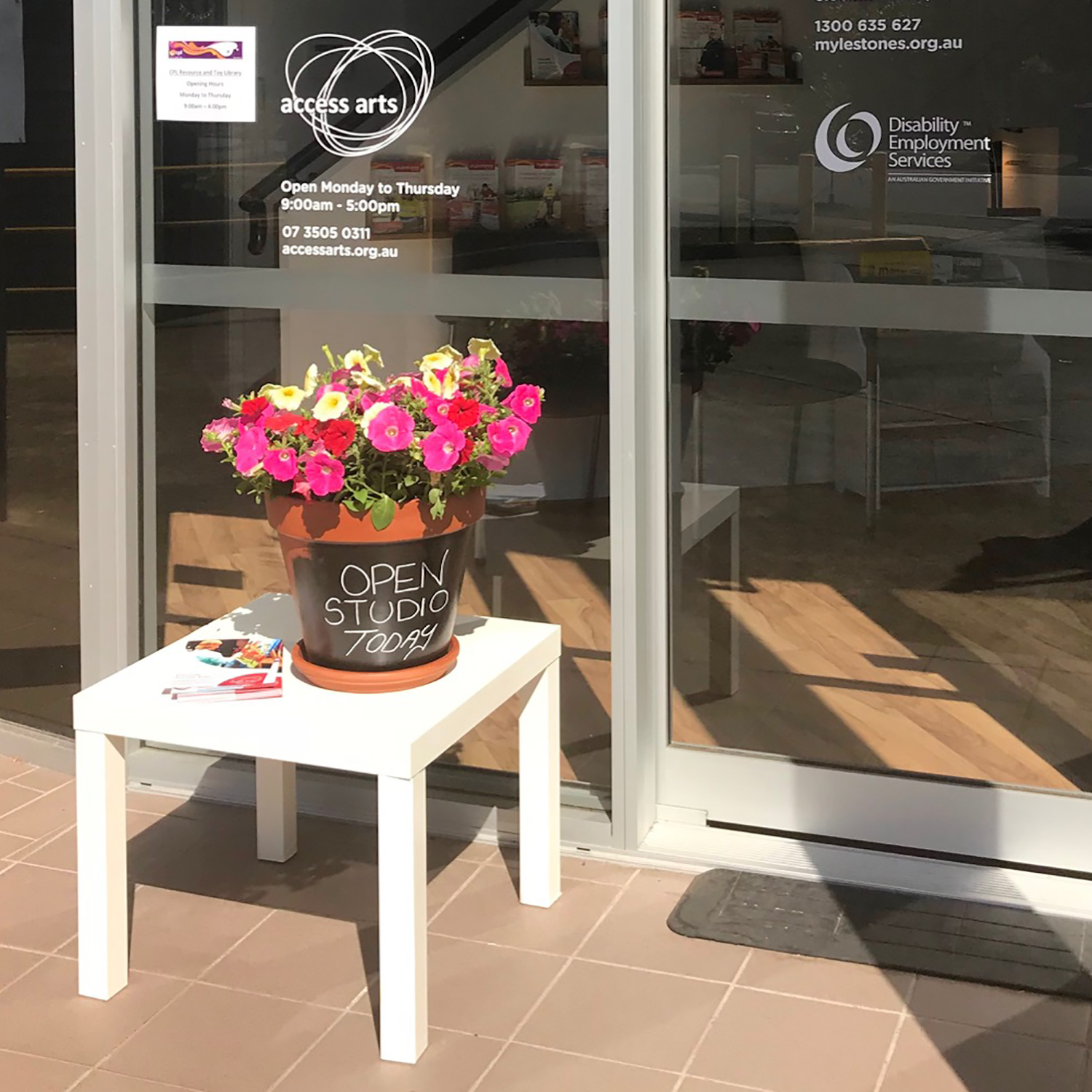 Flowerpot with bright flowers sitting on a white table outside sliding entrance doors