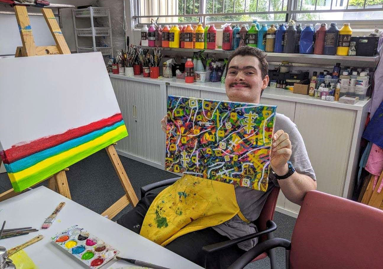 Young maYoung man showcasing paintingn showcasing painting