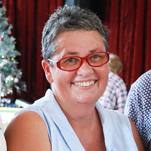 A cropped photo of Felicity wearing a sleeveless blue blouse and red glasses. She has short dark grey hair
