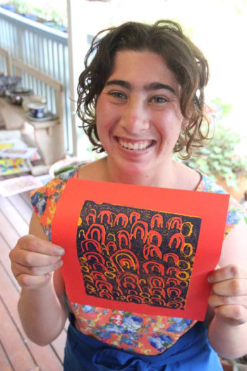 Freya holding up an orange sheet of paper with a pattern printed on it.