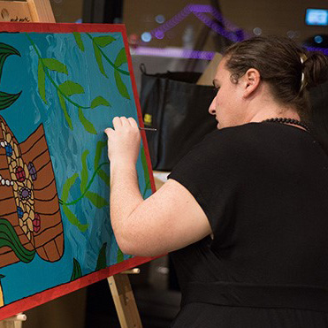 Woman wearing a black top painting a canvas
