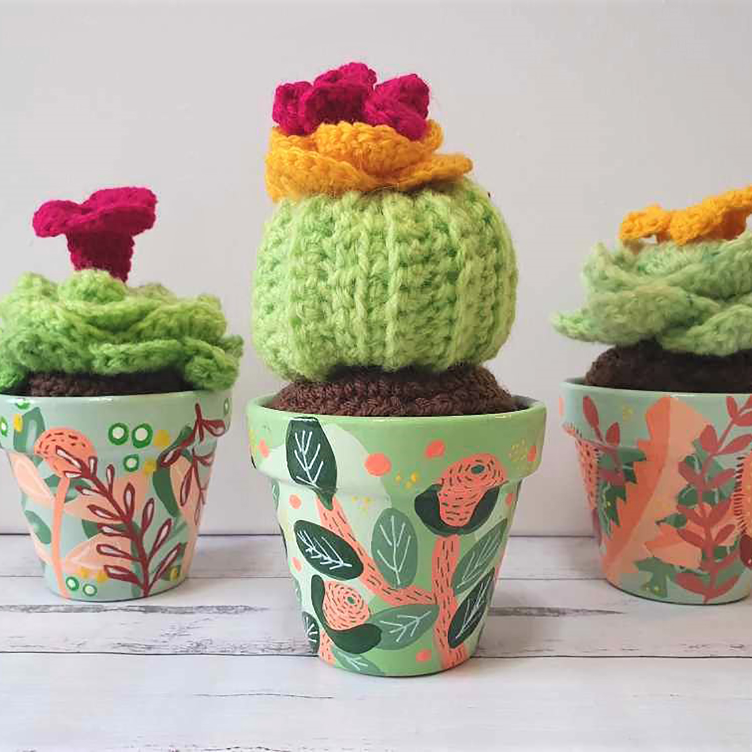 Three painted pots with crocheted cacti in them
