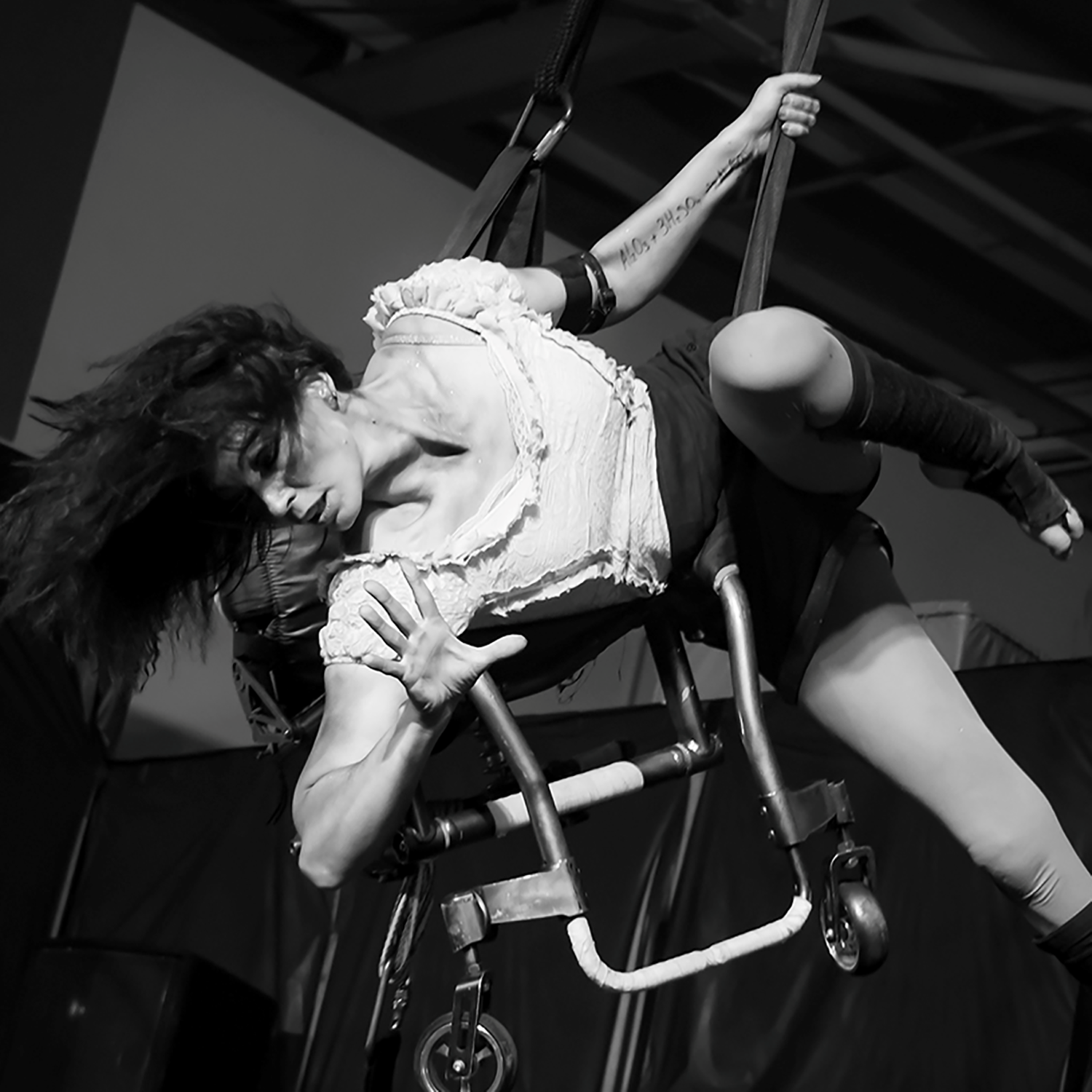 Lauren Watson pictured in black and white, performing an aerial routine with her wheelchair.