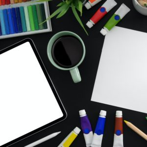 Desktop scattered with art supplies, a white sheet of paper an iPad and a coffee mug