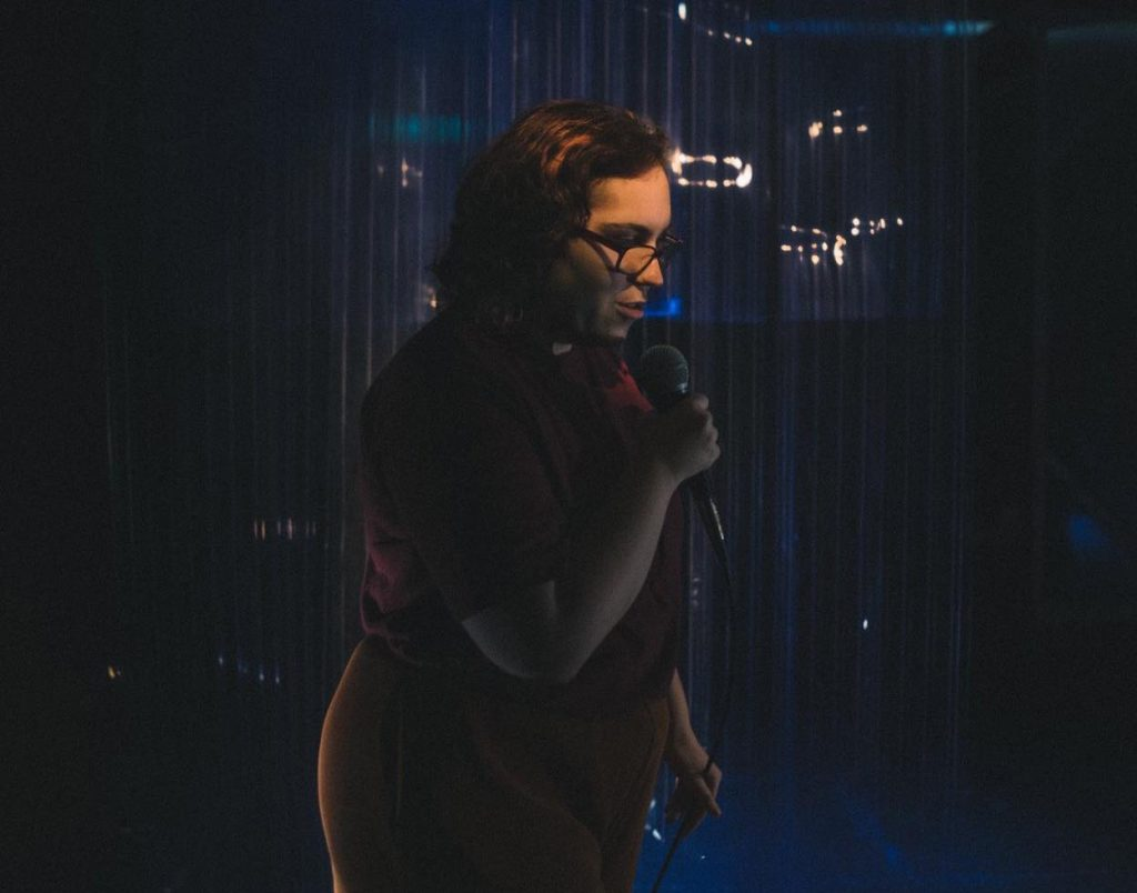 A dark image of Allycia on stage holding a microphone in one hand.