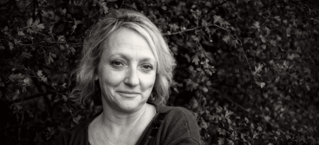 Sarah Pickthall pictured in black and white in front of a background of greenery. SHe is slightly off centre, looking at the camera.
